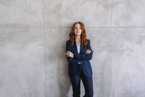 Portrait of confident redheaded businesswoman standing at a wall - KNSF06638