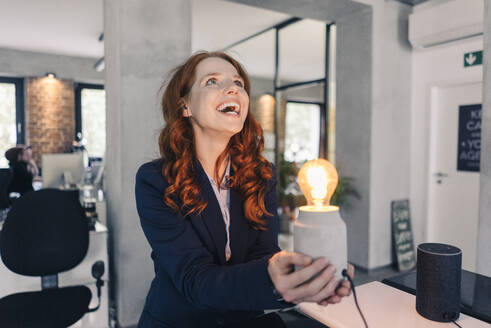 Laughing redheaded businesswoman holding lamp in office - KNSF06641