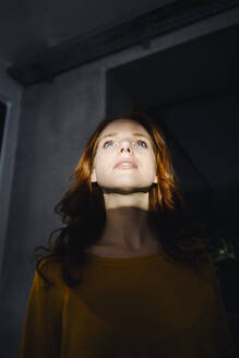 Redheaded woman with light and shadow looking up - KNSF06650