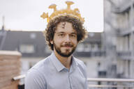 Portrait of confident businessman on roof terrace wearing a crown - KNSF06656