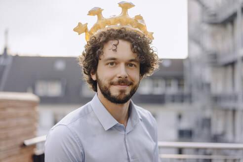 Portrait of confident businessman on roof terrace wearing a crown - KNSF06656