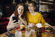Two female friends with cell phone having burger in a restaurant - KNSF06659