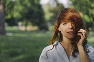 Portrait of a beautiful redheaded woman in a park - KNSF06665