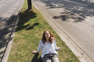 Redheaded woman sitting on grass verge - KNSF06677