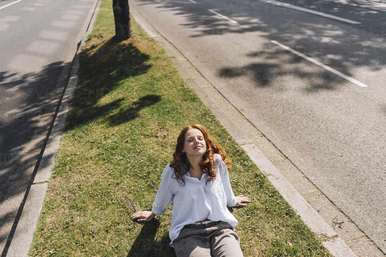 Redheaded woman sitting on grass verge - KNSF06677 - Kniel Synnatzschke/Westend61