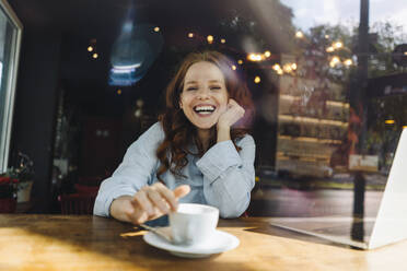 Portrait of happy redheaded woman with laptop in a cafe - KNSF06680