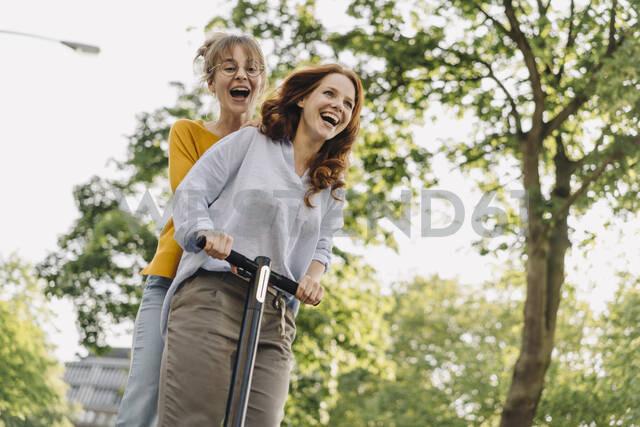 Happy female friends riding e-scooter together - KNSF06683 - Kniel Synnatzschke/Westend61