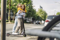 Young woman hugging friend on e-scooter in the city - KNSF06686