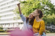 Two happy female friends taking a selfie in the city - KNSF06689