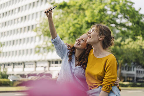 Two happy female friends taking a selfie in the city - KNSF06689