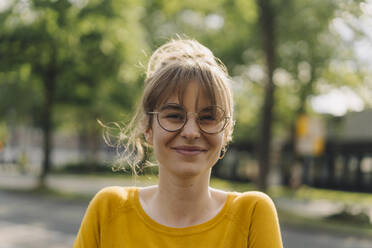 Portrait of smiling young woman with glasses - KNSF06692