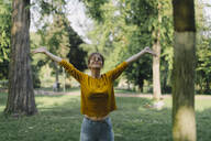 Young woman in a park with outstretched arms - KNSF06698