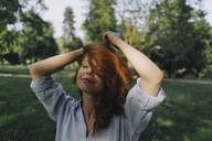 Portrait of redheaded woman in a park - KNSF06704