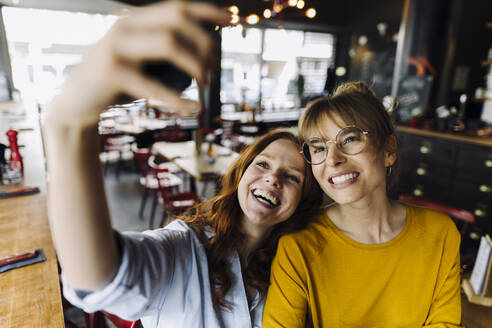 Two happy female friends taking a selfie in a restaurant - KNSF06707