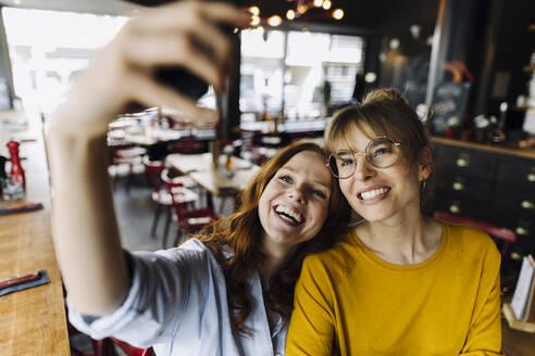 Two happy female friends taking a selfie in a restaurant - KNSF06707