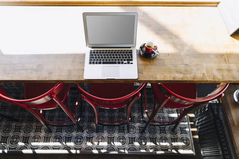 Laptop and cup of coffee on table in a cafe - KNSF06716
