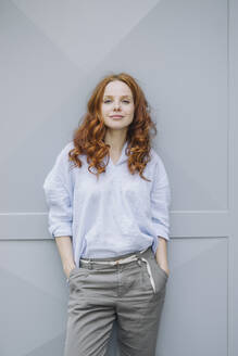 Portrait of beautiful redheaded woman standing at a wall - KNSF06719