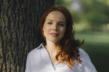 Portrait of redheaded woman at tree in a park - KNSF06725