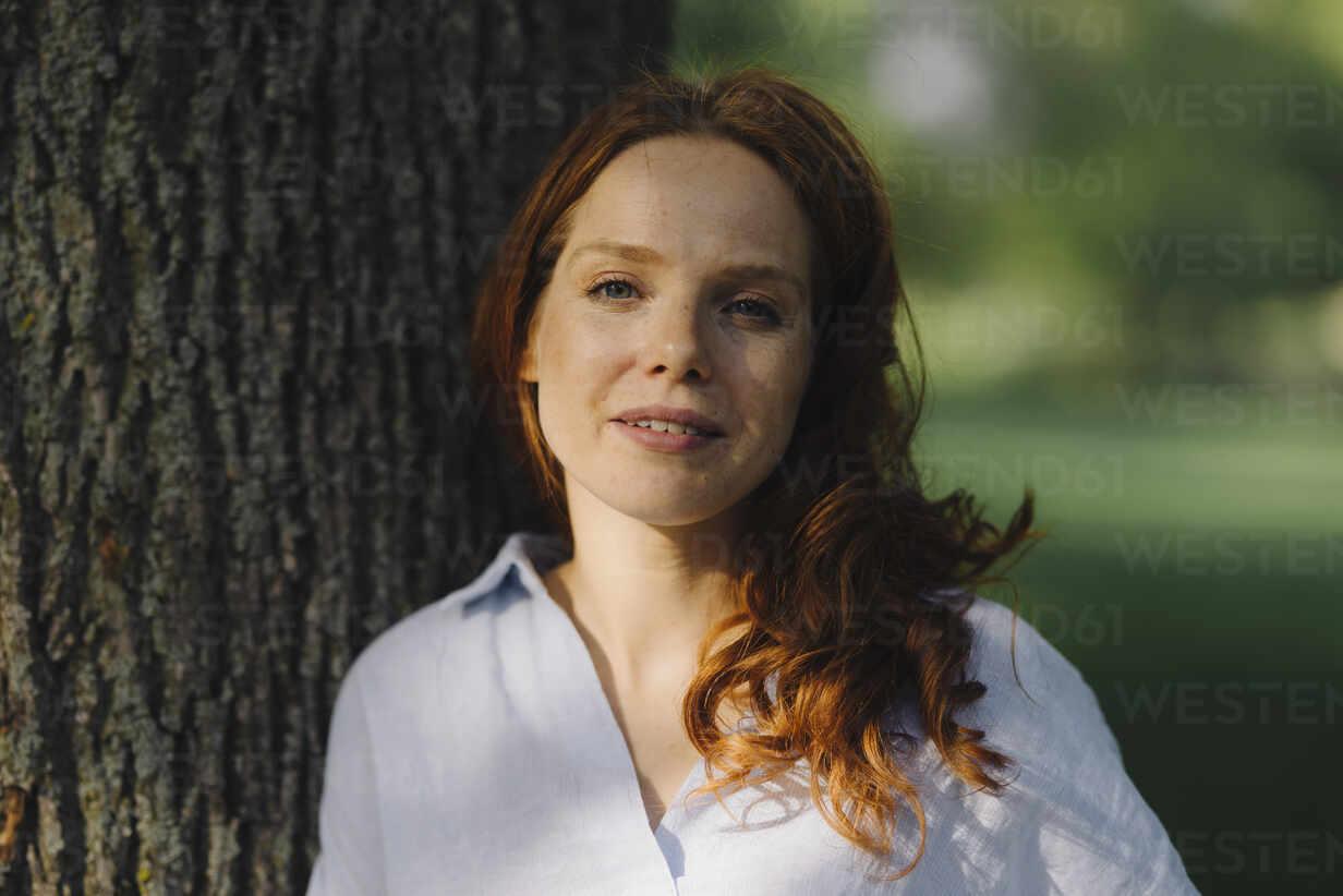 Portrait of redheaded woman at tree in a park - KNSF06725 - Kniel Synnatzschke/Westend61