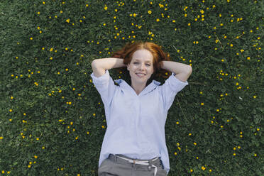 Portrait of redheaded woman lying on a flower meadow - KNSF06728