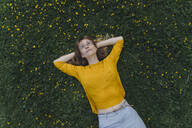 Young woman lying on a flower meadow - KNSF06731