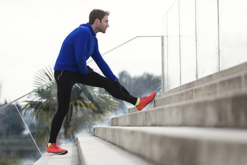 Jogger stretching his leg on steps - JSRF00634