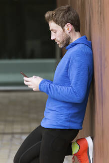 Jogger using his smartphone, leaning on a wall - JSRF00646