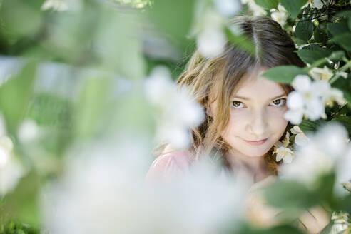 Portrait eines Mädchens an einem Strauch voller Blüten, Vilsbiburg, Bayern, Deutschland - STBF00408