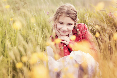 Portrait of smiling girl wearing red leather jacket crouching in flower meadow - STBF00411