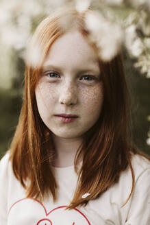 Red-haired teenage girl posing in orchard - JOHF01200