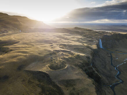Iceland, Aerial view of waterfall splashing down high cliff at sunset - DAMF00078