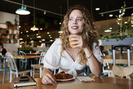 Smiling young woman in a cafe having breakfast - IGGF01331