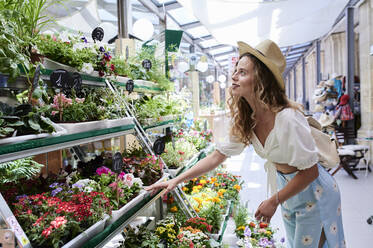 Young woman choosing flowers at a shop - IGGF01346