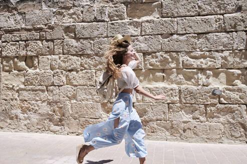 Happy young woman running along a wall - IGGF01352