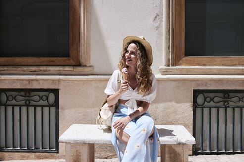 Young woman sitting on stone bench eating ice cream - IGGF01355