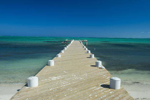 Diminishing perspective of pier over sea against clear blue sky during sunny day, Providenciales, Turks And Caicos Islands - RUNF03333