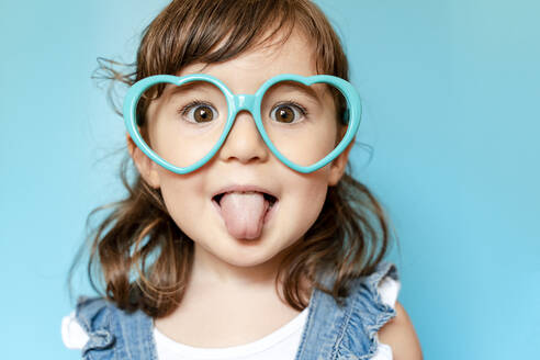 Portrait of cute little girl with tongue out and heart shaped glasses on blue background - GEMF03178