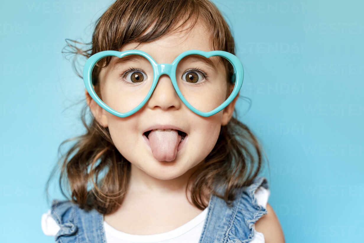 Portrait of cute little girl with tongue out and heart shaped glasses on blue background - GEMF03178 - Gemma Ferrando/Westend61