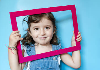 Portrait of cute little girl holding a picture frame on blue background - GEMF03181