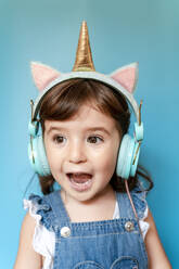 Portrait of cute little girl listening music and singing with unicorn shaped earphones on blue background - GEMF03184