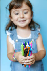 Portrait of cute little girl picking up a handful of colored ballpoint pens on blue background - GEMF03187