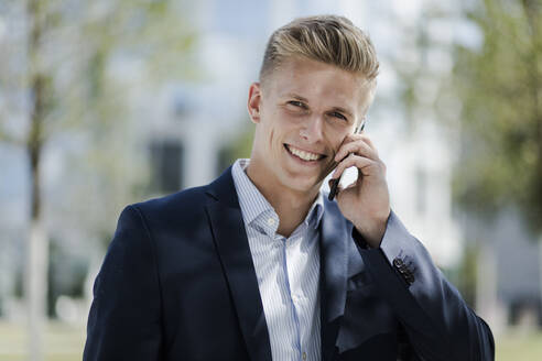 Portrait of smiling young businessman talking on cell phone - MOEF02488