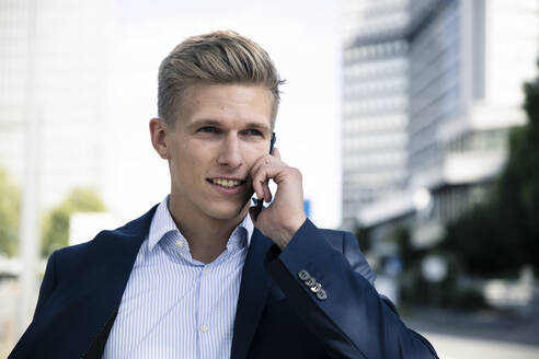 Young man talking on the phone in the city - MOEF02500