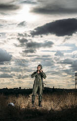 Man posing dressed as an astronaut on a meadow with dramatic clouds in the background - DAMF00082