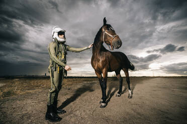 Man dressed as an astronaut with a horse on a meadow with dramatic clouds in the background - DAMF00088