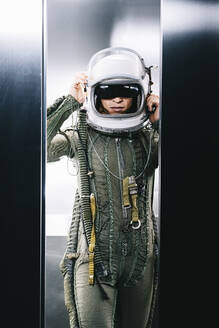 Man posing dressed as an astronaut in skyrocket elevator - DAMF00091