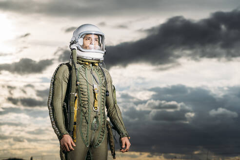 Man posing dressed as an astronaut with dramatic clouds in the background - DAMF00094