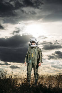 Man posing dressed as an astronaut on a meadow with dramatic clouds in the background - DAMF00097