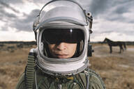 Man posing dressed as an astronaut on a meadow with dramatic clouds in the background - DAMF00100
