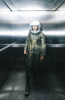 Man posing dressed as an astronaut in skyrocket elevator - DAMF00103